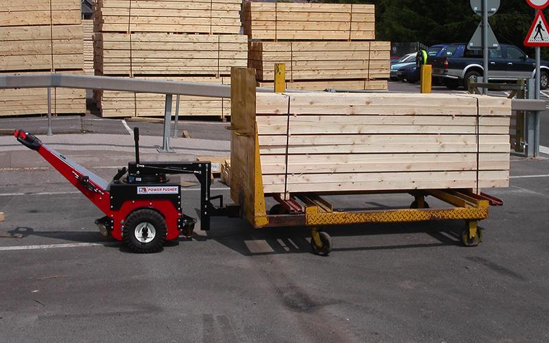 El empujador Power Pusher con brazo de dirección, moviendo un carro móvil de 2.500 kg cargado con madera de aserradero