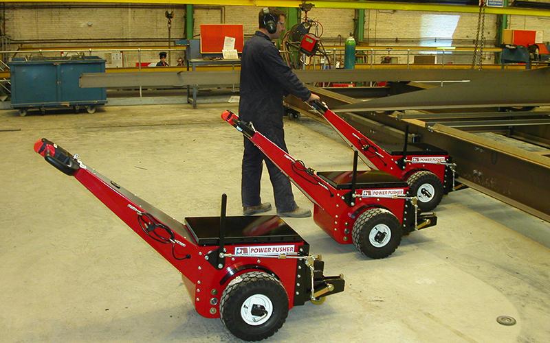El empujador Power Pusher, con accesorios a medida, empujando grandes producciones de acero a lo largo de una línea de producción basada en raíles