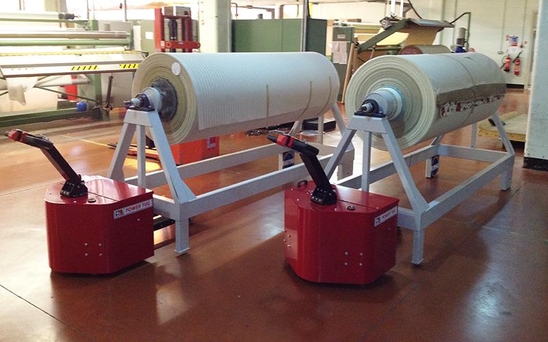 El empujador PowerTug moviendo carros de rollo de tela de 3.500 kg. Su sistema de elevación hace que sean innecesarios las ruedas delanteras de los carros