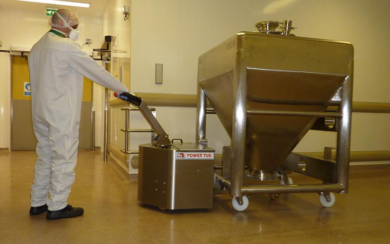 El empujador de acero inoxidable PowerTug moviendo un recipiente farmacéutico de 1.000 kg con 4 ruedas giratorias