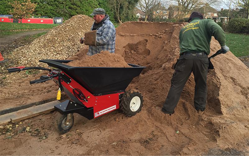 Utilizando la carretilla eléctrica para mover arena durante un proyecto de césped