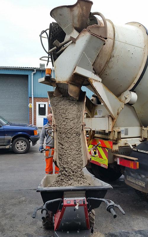 Cargando una carretilla eléctrica MUV con hormigón desde un camión
