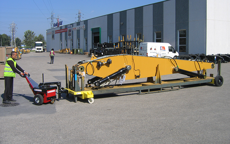 El empujador Power Pusher moviendo 3.500 kg de aguilón de la excavadora en un juego de ruedas orientables temporales para Caterpillar
