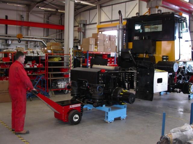 El empujador Power Pusher moviendo el chasis del vehículo todoterreno en patines a lo largo de la línea de producción