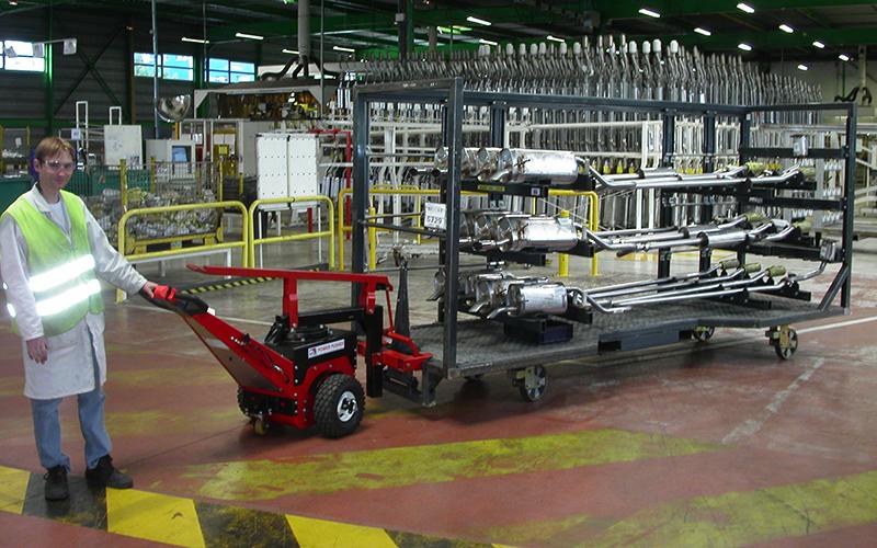 El empujador Power Pusher con brazo de dirección, moviendo un carro móvil de 1.100 kg cargado de conjuntos de escape para Faurecia