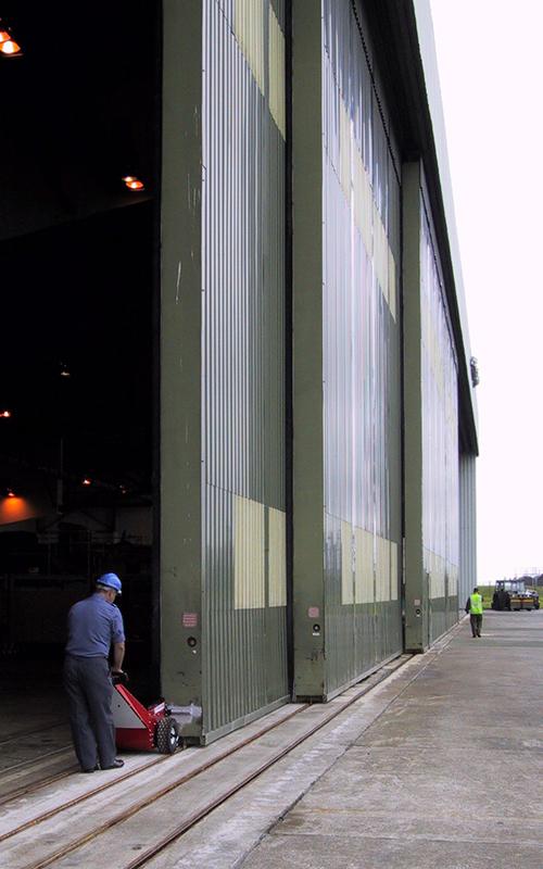 El empujador Power Pusher abriendo puertas de explosión de 40.000 kg de hangar de los aviones para RAF