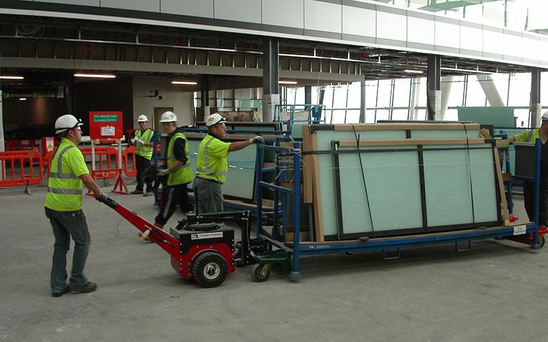El empujador Power Pusher con brazo de dirección, moviendo 2.500 kg de vidriado para Permasteelisa en Heathrow T5
