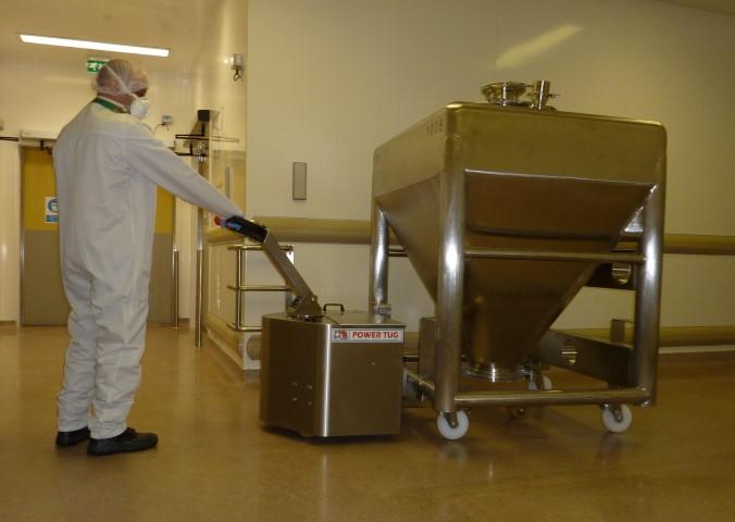 El empujador PowerTug de acero inoxidable moviendo un recipiente de mezcla farmacéutica de 1.000kg de GSK