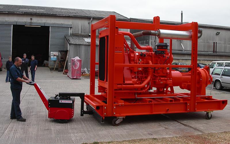 El empujador Super Power Pusher con brazo de dirección, moviendo una bomba industrial de 8.000 kg en un patín para Bombas Xylem