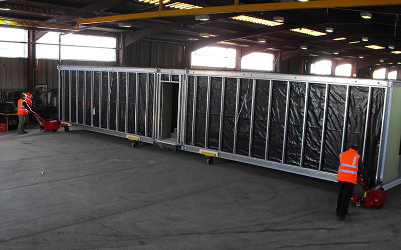 El empujador Super Power Pusher moviendo edificios modulares en patines a los largo de la línea de producción en Rollalong